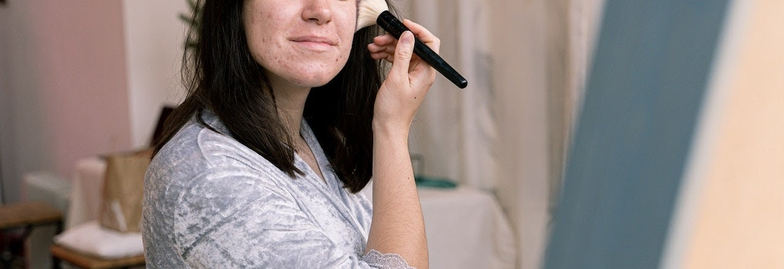 Woman putting makeup on over acne I'm Not a Teenager: How Am I Still Getting Acne?