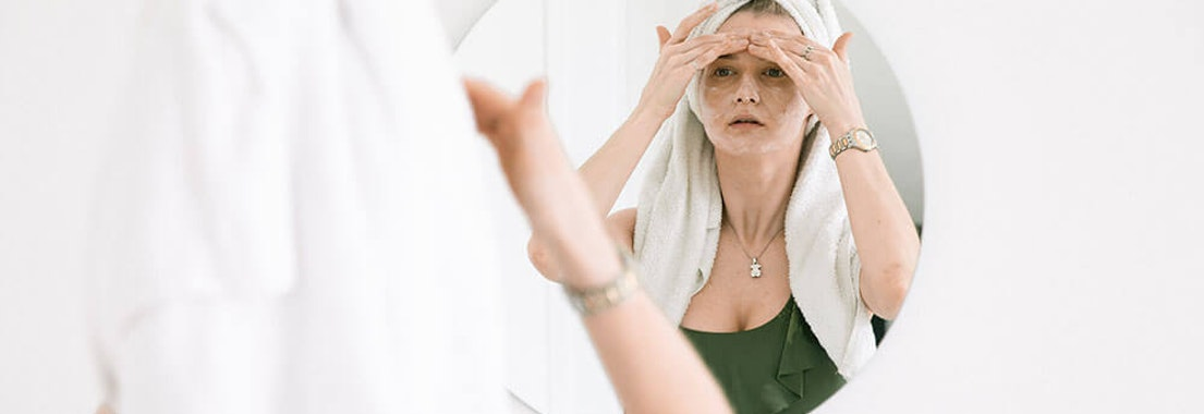 Woman applying dehydrated skin treatment Is Your Skin Dehydrated? How to Spot & Treat This Issue