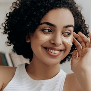 Woman smiling applying facial cream At What Age Should You Start Regularly Seeing a Dermatologist?