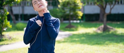 Woman scratching at a sweat rash on her neck How to Deal with Rashes from Exercise