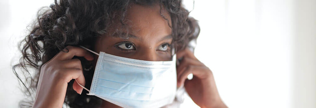 Woman putting on a mask How to Stop Face Masks/PPE From Irritating Your Skin