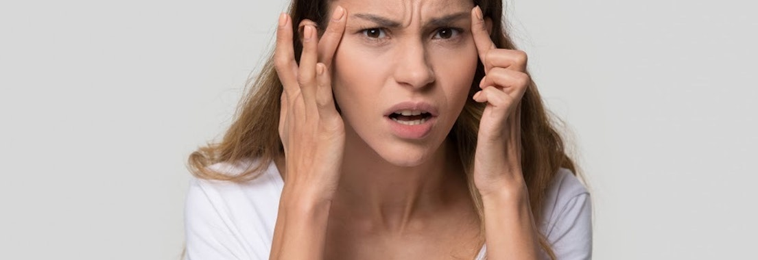 Woman looking at wrinkles on her face How to Reduce Wrinkles After They've Appeared
