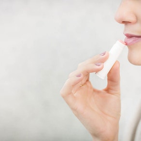 Woman applying chapstick to chapped lips 5 Ways to Prevent Dry & Chapped Lips