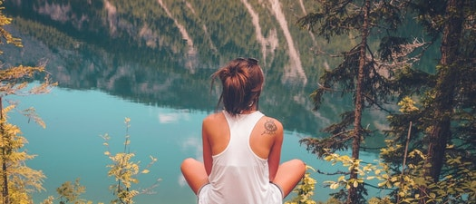 Woman with a tattoo sitting on a cliff Why Winter Is the Perfect Time to Start Tattoo Removal
