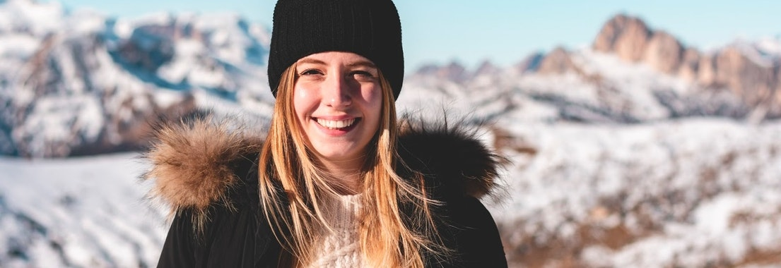 Woman standing on a mountain in Winter How Dermal Optical Thermolysis (DOT) Can Help Your Skin This Winter