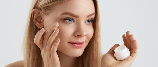 Woman applying dark spot treatemt to her face How to Decrease Dark Spots and Under Eye Circles