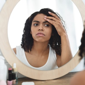 Woman looking in the mirror for aging skin How to Know Whether or Not You're Aging Well