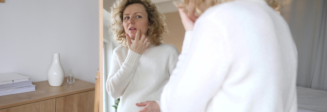 Woman feeling her skin in the mirror Acne and Pregnancy: How to Treat It Safely