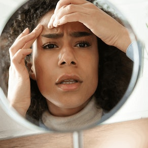 Stressed woman looking in the mirror How Stress Affects Pre-Existing Skin Conditions