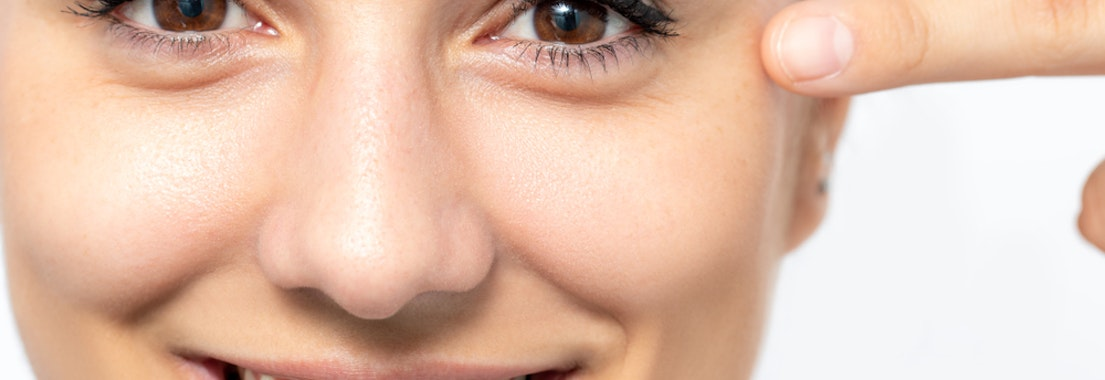 Woman feeling her face for botox How to Use Botox for Wrinkle Prevention