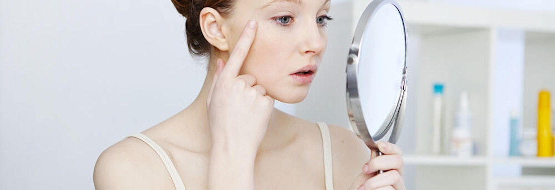 Woman looking in the mirror at Crow's Feet Say Goodbye to Crow's Feet With These Treatments