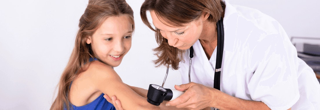Dermatologist looking at a young girl's arm What Age Should I Start Regularly Seeing a Dermatologist?