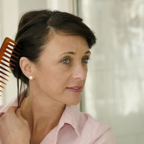 Woman analyzing her scalp Female Hair Loss? We Can Help!