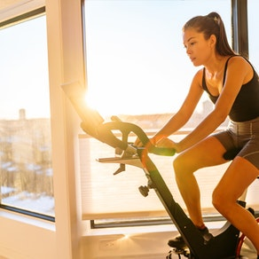 Woman riding a Peloton bike How to Deal with Rashes and Hives from Exercise