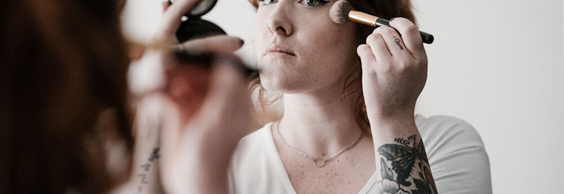 Woman applying makeup Can Cosmetic Dermatology Treatments Replace Makeup?