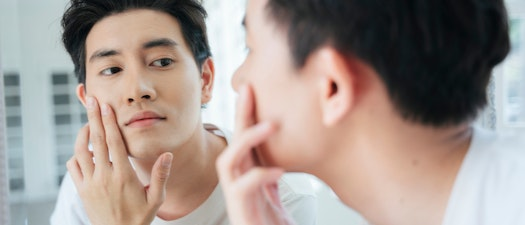 Man feeling oily skin in the mirror Top Tips for Managing Oily Skin Year-Round