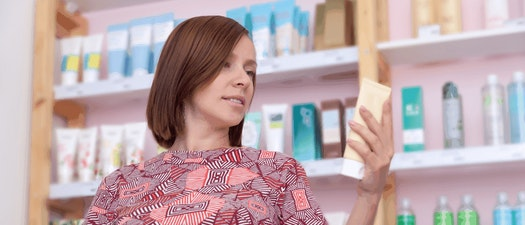 Woman looking at skin care product Best Skin Products for Pregnancy and Breastfeeding
