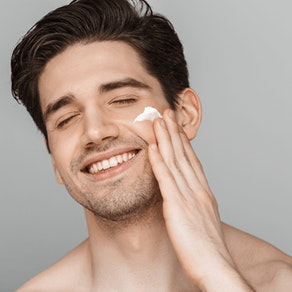 Man applying cream to acne Why Acne Can Worsen in the Summer