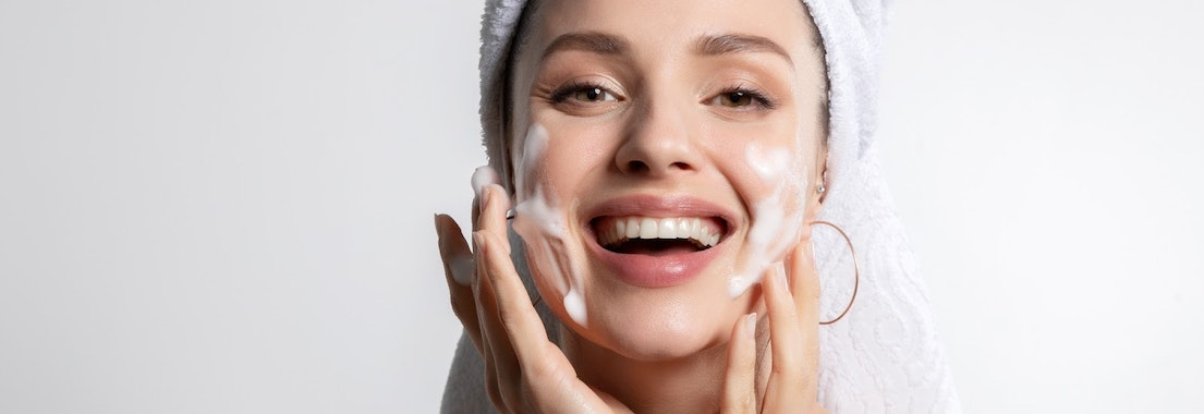 Woman smiling doing her skin care routine How to Know If Your Skincare Routine Is Working