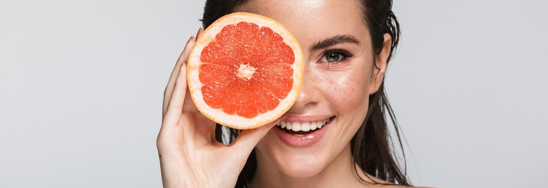 Woman holding a grapfruit in front of her face How Eating Fruits and Veggies Rejuvenates Your Skin