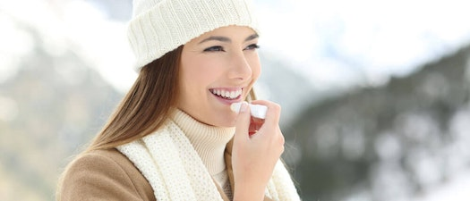 Woman applying chapstick to chapped lips 5 Tips for Preventing Dry, Cracked Lips
