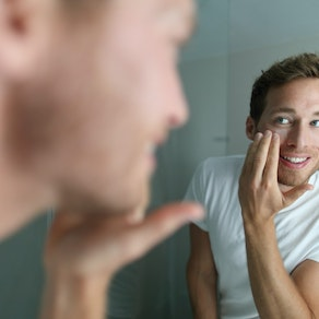 Man looking in the mirror at acne Best Winter Skin Care for Acne Prone Dry Skin