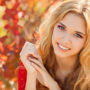 Woman standing in fall leaves Enjoy a Fall Facial and Look Your Best This Season