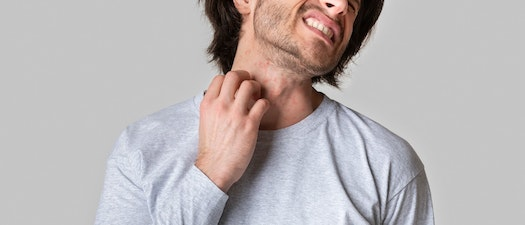 Man scratching at neck rash How to Deal with Rashes from Exercise