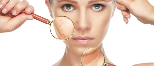 Woman looking at her skin through a magnifying glass How to Know Whether You're Aging Well or Not