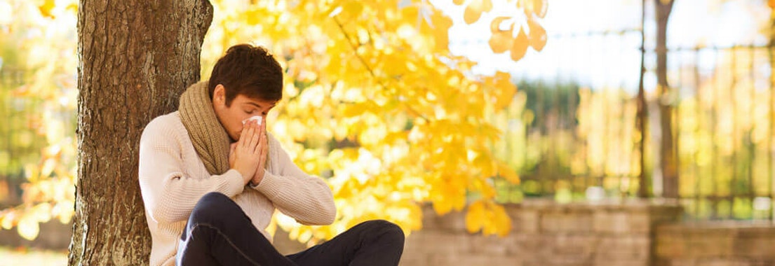 Man blowing his nose from allergies outside Is Your Skin issue Actually Caused by Seasonal Allergies?