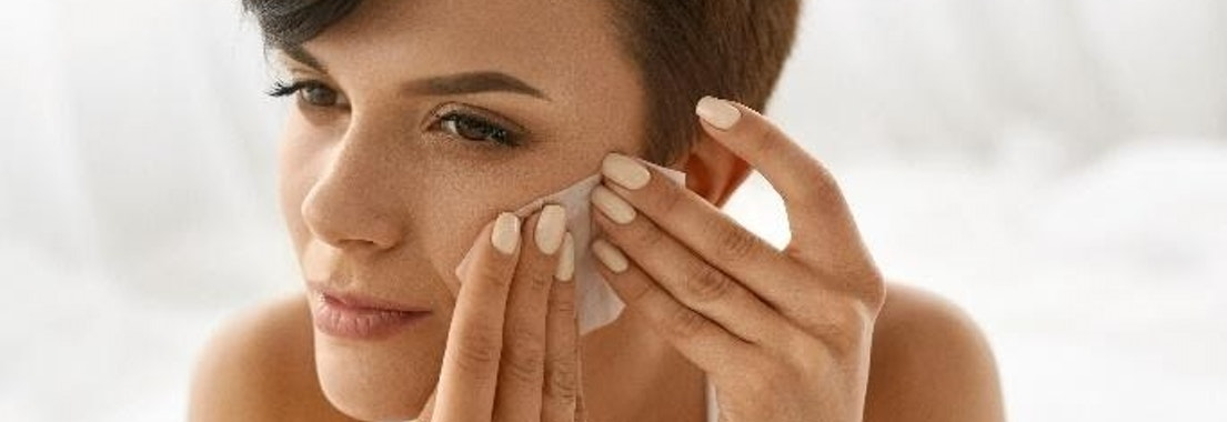 Woman applying cream to oily skin Top Tips for Managing Oily Skin Year-Round