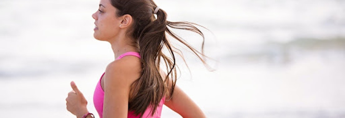 Woman exercising on the beach How to Deal with Rashes from Exercise