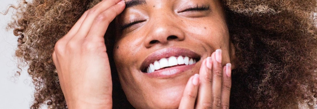 Woman feeling her face after facial treatment What Facials Can Do For Your Skin After a Hot Summer