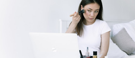 Woman doing her makeup in the mirror Try Dermaplaning in Time for Springtime Makeup Trends