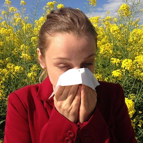 Woman with seasonal allergies blowing her nose How Seasonal Allergies Affect Your Skin