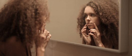 Woman looking at acne Acne as a Teen? Try Dermaplaning
