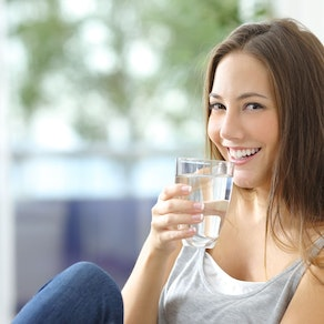 Woman smiling and drinking water What Does Water Really Do for the Skin?