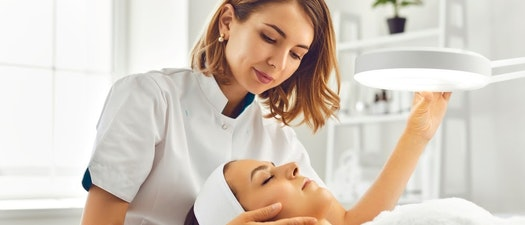 Dermatologist looking at a woman's skin What Age Should I Start Regularly Seeing a Dermatologist?