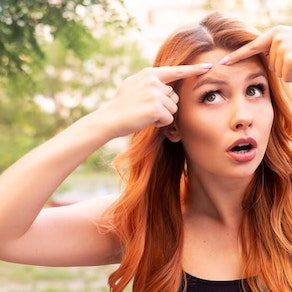 Woman looking at acne in summer Why Acne Can Worsen in the Summer
