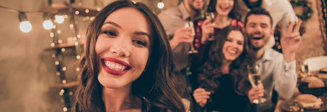 Group of friends at holiday party Be Confident at Your Holiday Party with These Acne Treatments
