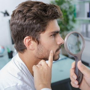 Man having face examined by dermatologist What Age Should I Start Regularly Seeing a Dermatologist?