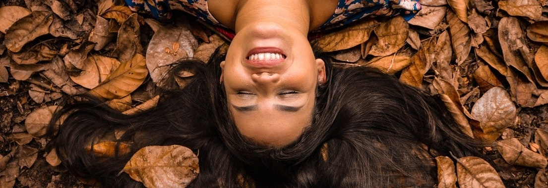 Girl with clear skin in autumn leaves Enjoy a Fall Acne Facial and Look Your Best This Season