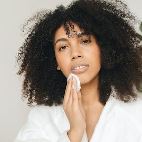 Woman applying treatment to oily skin Top 7 Tips for Managing Oily Skin Year-Round