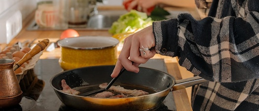 Woman cooking bacon on the stove What Processed Meats Can Do to Your Skin