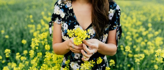 Woman standing in field of flowers How Seasonal Allergies Affect Your Skin
