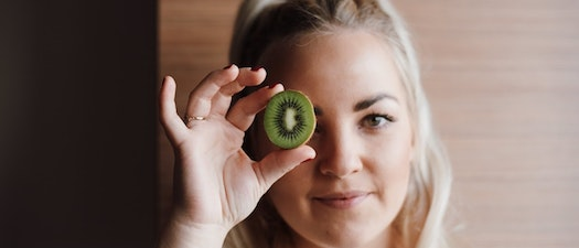 Woman holding a kiwi in front of her face How Eating Fruits and Veggies Rejuvenates Your Skin