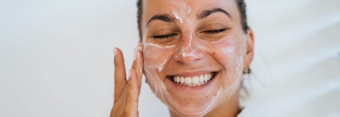 Woman applying skin cream to her face Acne as a Teen? Here Are Some Tips for Clear Adult Skin