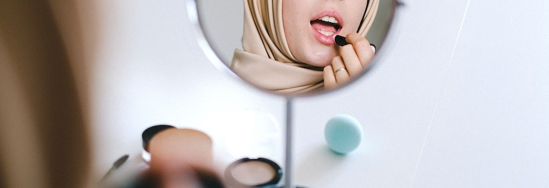 Woman looking in the mirror using botox filler How Not to Overdo Botox and Fillers