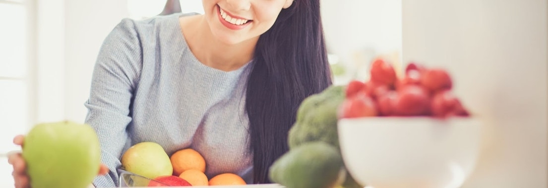 Woman picking out fruits How Eating Fruits and Veggies Rejuvenates Your Skin