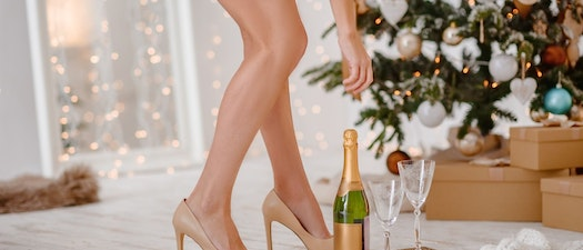 Woman standing by a holiday tree Feel Confident in Your Holiday Dress with Laser Hair Removal